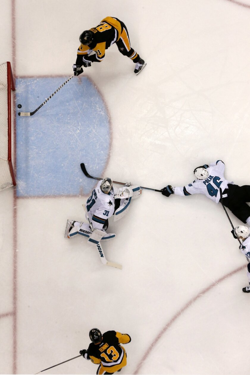 Pittsburgh Penguins' Phil Kessel (81) takes a pass from teammate Nick Bonino (13) and backhands it into the net for a goal behind San Jose Sharks goalie Martin Jones (31) and defenseman Roman Polak (46) during the second period of Game 2 of the NHL hockey Stanley Cup Finals on Wednesday, June 1, 20
