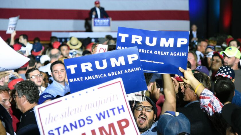 A protester is surrounded by Trump supporters as he tries to disrupt a rally for then-presidential candidate Donald Trump on March 13, 2016, in Florida.