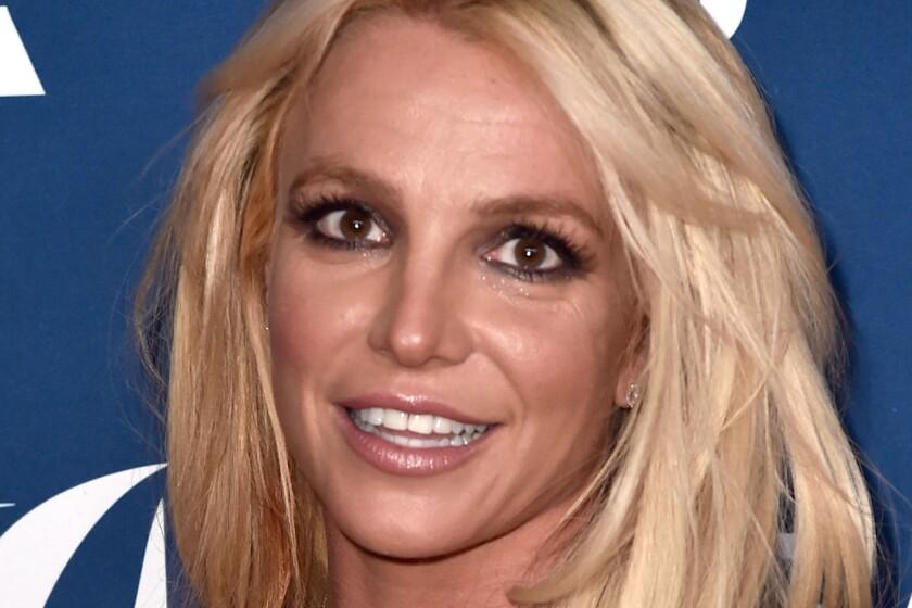 The face of a blond woman wearing dark eye makeup