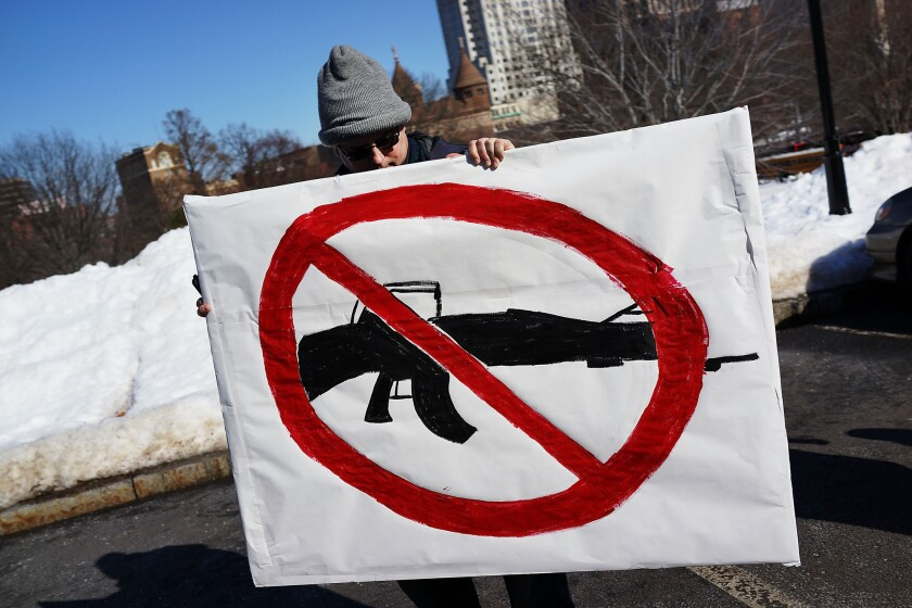 A man holds up a sign with a depiction of an assault weapon during a rally at the Connecticut State Capital to promote gun control legislation in the wake of the Dec. 14 school shooting in Newtown.