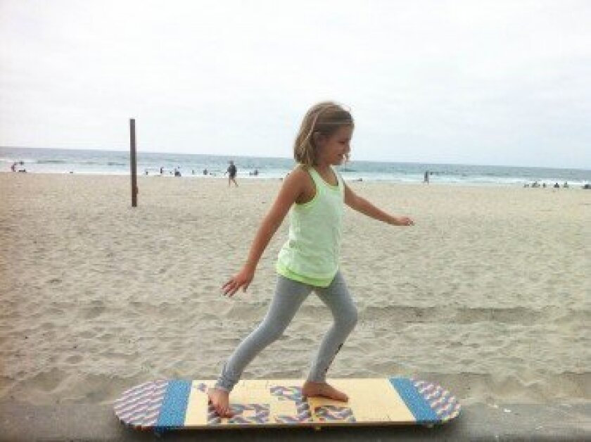 La Jolla resident Ripples Turquand, 8, tries out a prototype Milkshake Board, a yoga balance board she designed for children and adults, with help and encouragement from her father, Glynn Turquand. Courtesy Photos