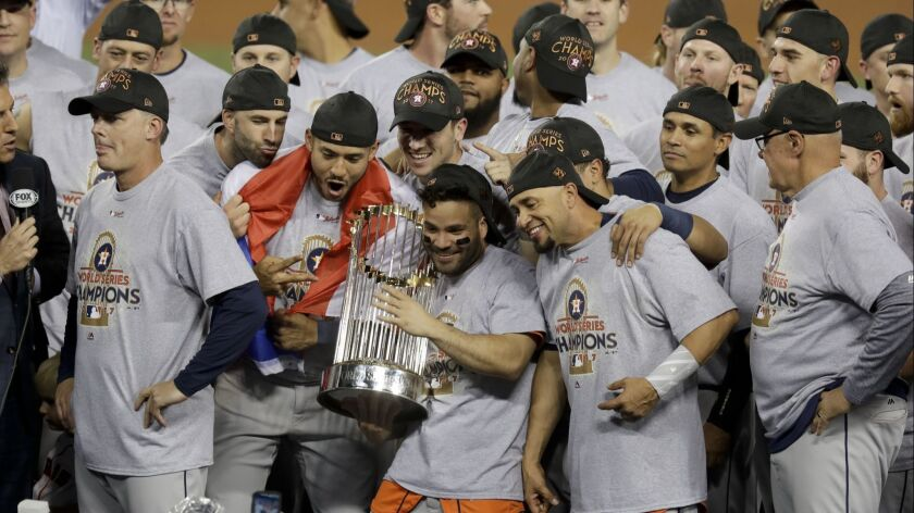 The Houston Astros celebrate with the World Series trophy after their Game 7 victory over the Los Angeles Dodgers.