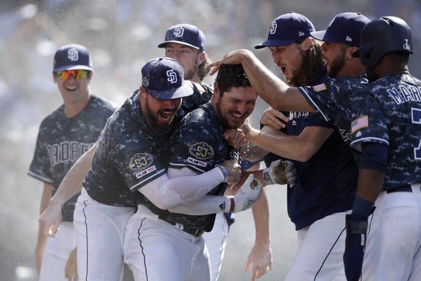 San Diego Padres' Hunter Renfroe, center, celebrates with teammates after hitting a walkoff grand slam against the Los Angeles Dodgers, May 5, 2019.