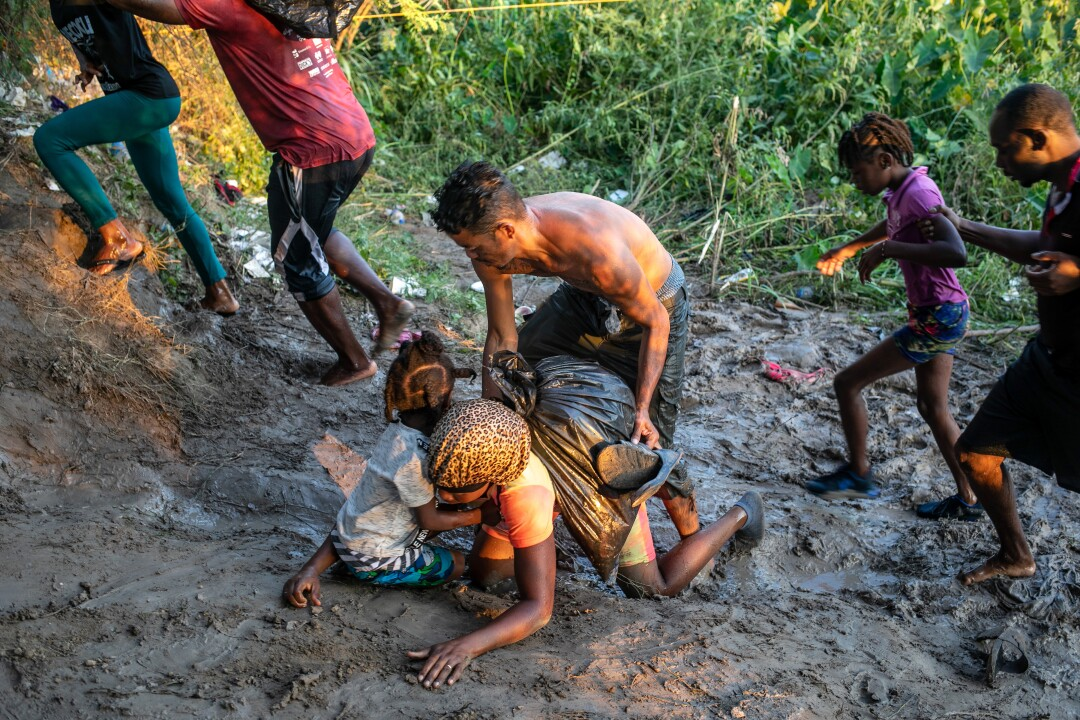 A Haitian immigrant falls in the mud after wading across the Rio Grande and back onto Mexico's shore.