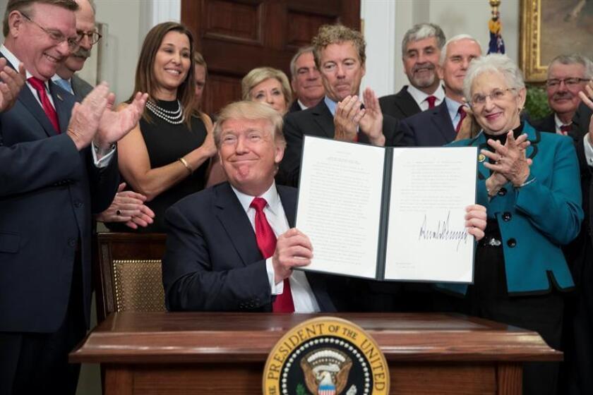 """El presidente de Estados Unidos, Donald Trump (c), posa tras firmar una orden ejecutiva diseñada para """"aliviar"""" a los ciudadanos ante algunos requisitos de Obamacare, la reforma de salud promulgada en 2010 por su predecesor, Barack Obama. EFE/Archivo"""