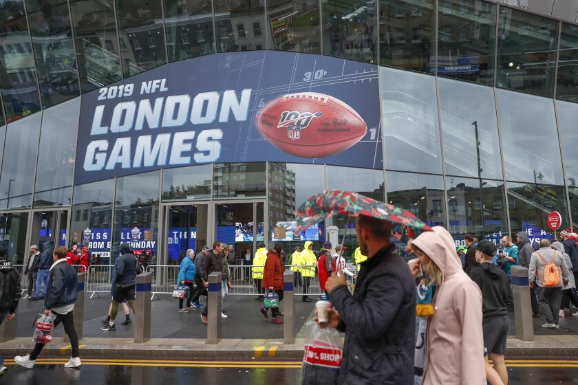 FILE - NFL football fans arrive at Tottenham Hotspur Stadium to watch an NFL football game between the Tampa Bay Buccaneers and the Carolina Panthers in London, in this Sunday, Oct. 13, 2019, file photo. The NFL is returning to London in October. The first game in London since the coronavirus pandemic will be played on Oct. 10 as the Atlanta Falcons face the New York Jets. A week later, the Jacksonville Jaguars meet the Miami Dolphins. Both games will be played at the stadium of Premier League soccer team Tottenham. The Falcons and the Jaguars will be the home teams. (AP Photo/Alastair Grant, File)