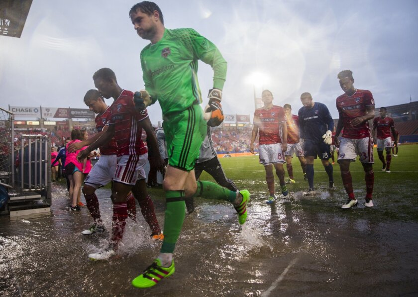 FC Dallas and Houston Dynamo players exit the field for a weather delay during the first half of a MLS soccer game on Thursday, June 2, 2016, in Frisco, Texas.  (Ashley Landis/The Dallas Morning News via AP) MANDATORY CREDIT; MAGS OUT; TV OUT; INTERNET USE BY AP MEMBERS ONLY; NO SALES