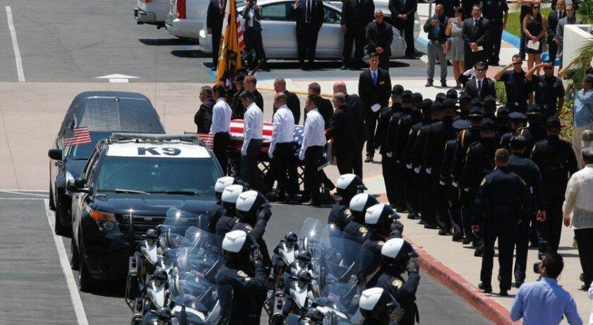 The body of slain police officer Jonathan De Guzman is carried out of Corpus Christi Church in Bonita.