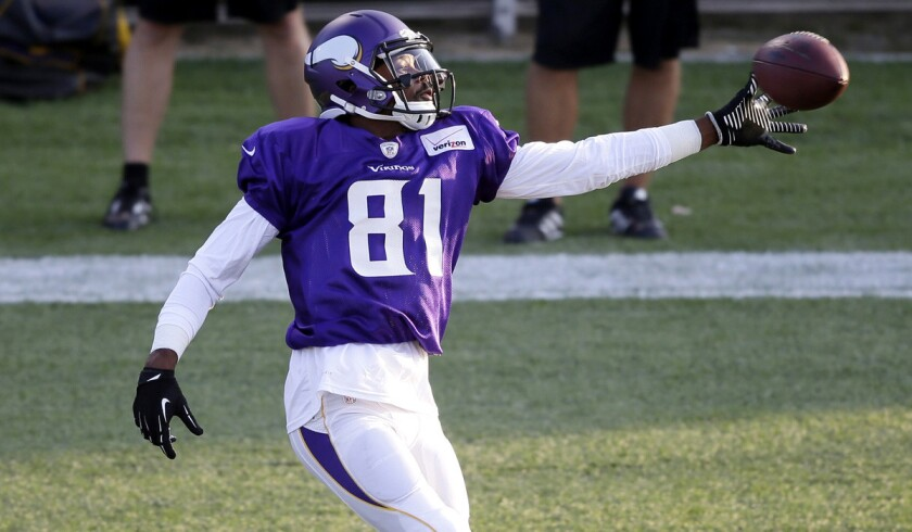 Vikings receiver Jerome Simpson reaches for a pass during summer camp.