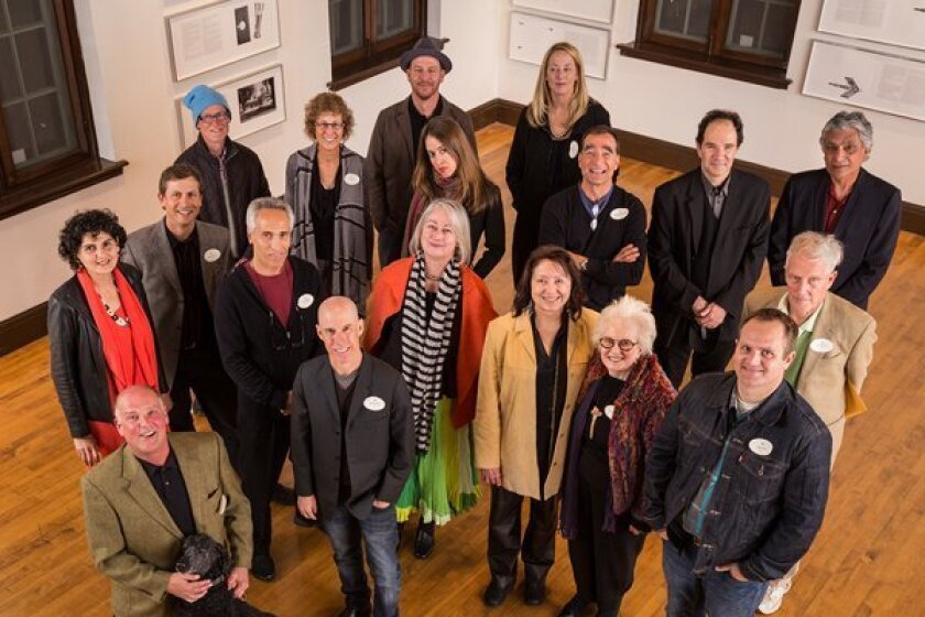 """Some of the artists in the Athenaeum's new book, """"Selections from the Permanent Collection: 1990-2010. Back Row (from left): Kim MacConnel (blue hat), Gail Roberts, Dave Adey (hat), Alida Cervantes (tilted head), Jean Lowe, Philipp Scholz Rittermann (in front of Jean), Ernest Silva, Raul Guerrero Next Row (from left): Doris Bittar (red scarf), Roman de Salvo; Ken Goldman; Patricia Patterson (striped scarf), Becky Cohen, Joyce Cutler-Shaw, Adam Belt, James Hubbell (standing behind Adam) In Front: Jay Johnson (left) with dog Monkey and Stephen Curry Photo: Roy Porello/Athenaeum Music & Arts Library"""