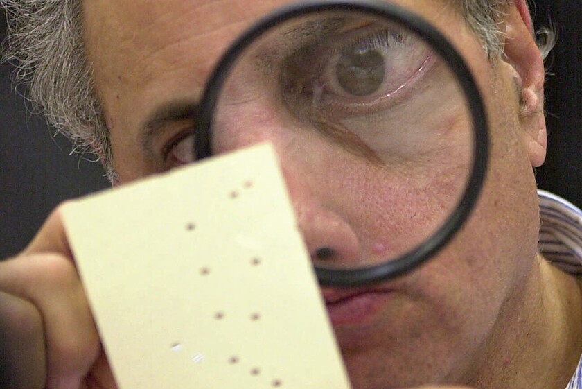 FILE - This Nov. 24, 2000 file photo shows Broward County canvassing board member Judge Robert Rosenberg using a magnifying glass to examine a disputed ballot at the Broward County Courthouse in Fort Lauderdale, Fla. Twenty years ago, in a different time and under far different circumstances than today, it took five weeks of Florida recounts and court battles before Republican George W. Bush prevailed over Democrat Al Gore by 537 votes. (AP Photo/Alan Diaz, File)