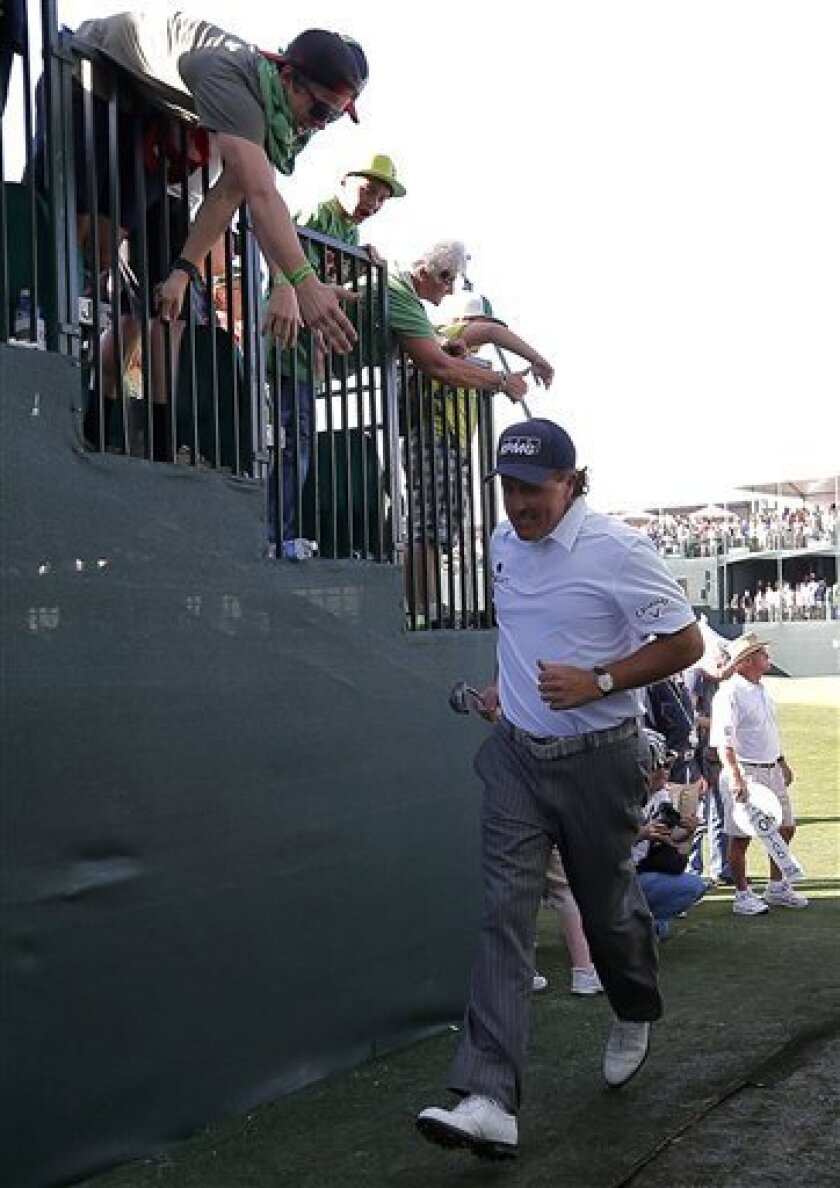 Phil Mickelson runs to the 17th tee from the 16th green during the third round of the Waste Management Phoenix Open golf tournament on Saturday, Feb. 2, 2013, in Scottsdale, Ariz. (AP Photo/Matt York)