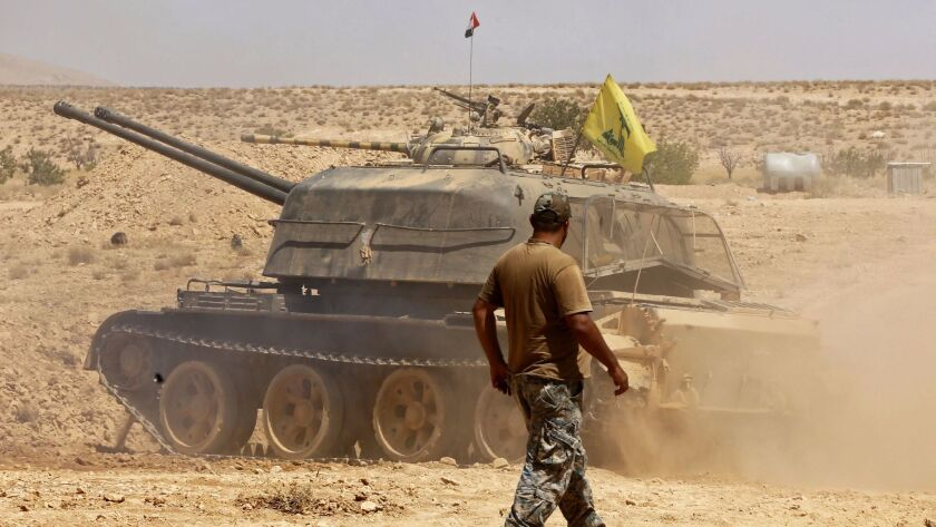 A fighter walks past a tank bearing a Hezbollah flag in the Qara area, in Syria's Qalamoun region, on Aug. 28, 2017.