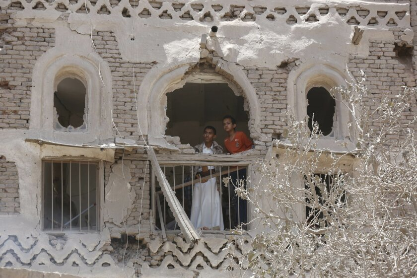 Residents look out from a window of their house that was damaged in a Saudi-led airstrike in Sanaa, Yemen, Saturday, Sept. 19, 2015. The overnight airstrikes against Yemen's Shiite rebels and their allies have killed almost 30 people, including civilians, in the capital Sanaa, security and medical officials there said Saturday. The coalition's overnight airstrikes hit an apartment building in the center of the capital, a UNESCO world heritage site, killing a family of nine, the officials who remain neutral in the conflict that has divided Yemen's security forces said. (AP Photo/Hani Mohammed)