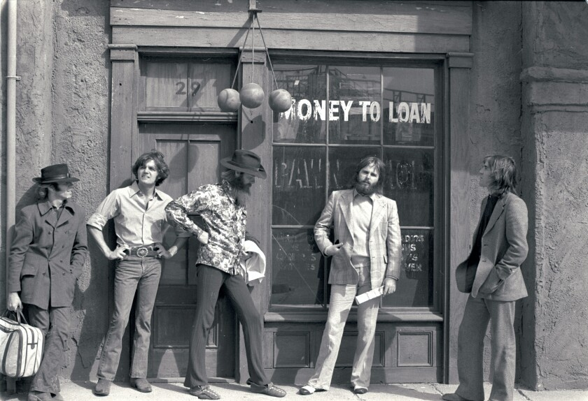 The Beach Boys stand outside a pawn shop, circa 1970, in a black-and-white photo.