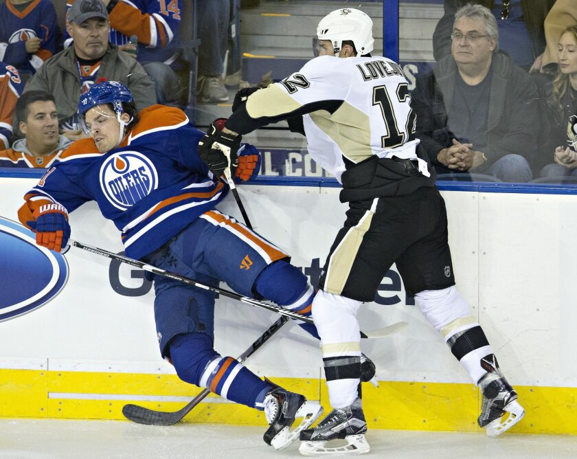 Pittsburgh Penguins' Ben Lovejoy (12) checks Edmonton Oilers' Anton Lander (51) during the second period of an NHL hockey game Friday, Nov. 6, 2015, in Edmonton, Alberta. (Jason Franson/The Canadian Press via AP)