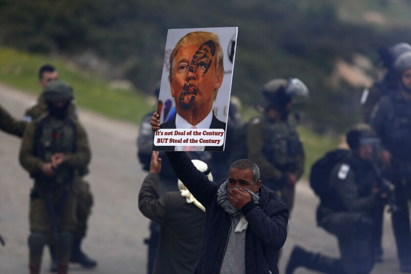 File - In this Tuesday, Feb. 25, 2020 file photo, a Palestinian demonstrator covers his face from tear gas fired by Israeli forces as he holds a poster of -U.S. President Donald Trump during a protest against President Donald Trump's Mideast initiative, in Jordan Valley in the West Bank. Israeli Prime Minister Benjamin Netanyahu has vowed to annex the valley and all of Israel's far-flung West Bank settlements, in line with President Donald Trump's Middle East plan, which overwhelmingly favors Israel and has been rejected by the Palestinians. (AP Photo/Majdi Mohammed, File)