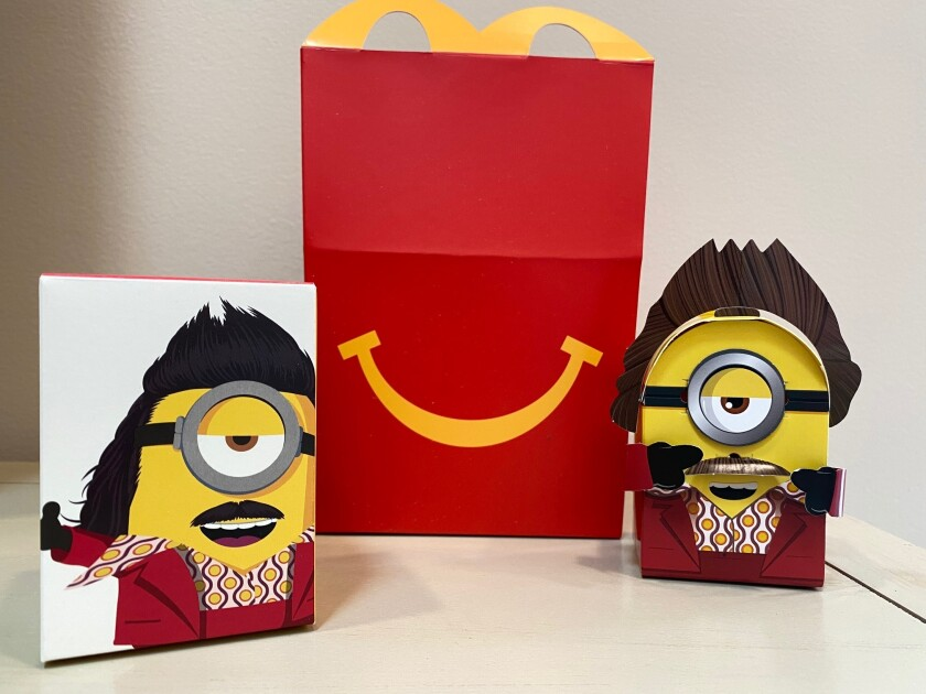 """A cardboard McDonald's Happy Meal toy is shown with a Happy Meal box on Sept. 20, 2021. McDonald's plans to """"drastically"""" reduce the plastic in its Happy Meal toys worldwide by 2025. The burger giant said Tuesday, Sept. 21 it's working with toy companies to develop new ideas, such as three-dimensional cardboard superheroes kids can build or board games with plant-based or recycled game pieces. (AP Photo/Dee-Ann Durbin)"""