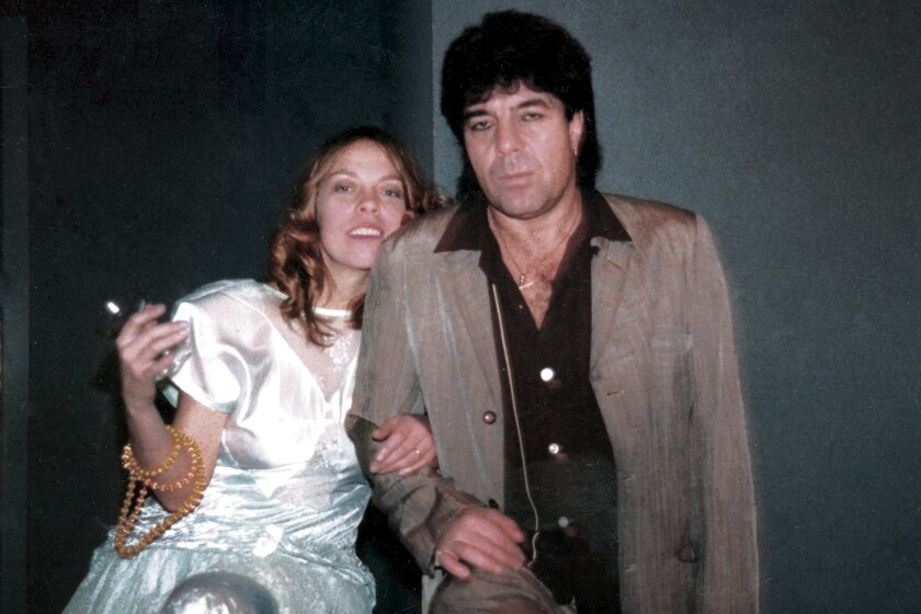 A woman in a white silk dress, left, leans against a man wearing a brown coat and brown shirt