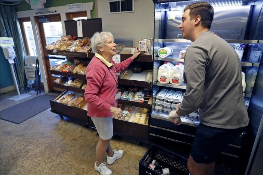 Volunteers stock pastries and dairy items at the Laguna Food Pantry in Laguna Beach.