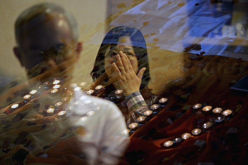 FILE - In this Friday, July 18, 2014 file photo, people pray for the victims of Malaysia Airlines Flight 17 at a church in Kuala Lumpur, Malaysia. The families of six crew members on a Malaysian passenger jet shot down over Ukraine nearly two years ago have filed lawsuits against Malaysia Airlines