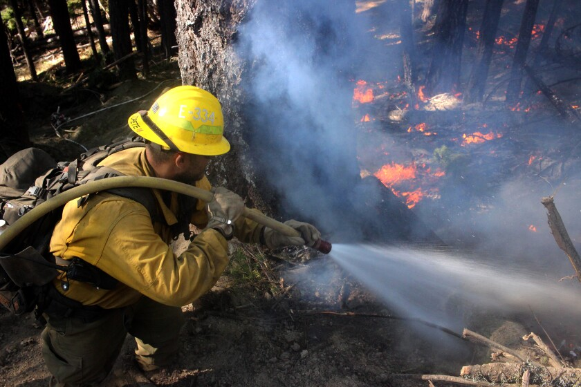 A firefighter sprays flames on the northwest flank of the August Complex fire in Trinity County on Sept. 22