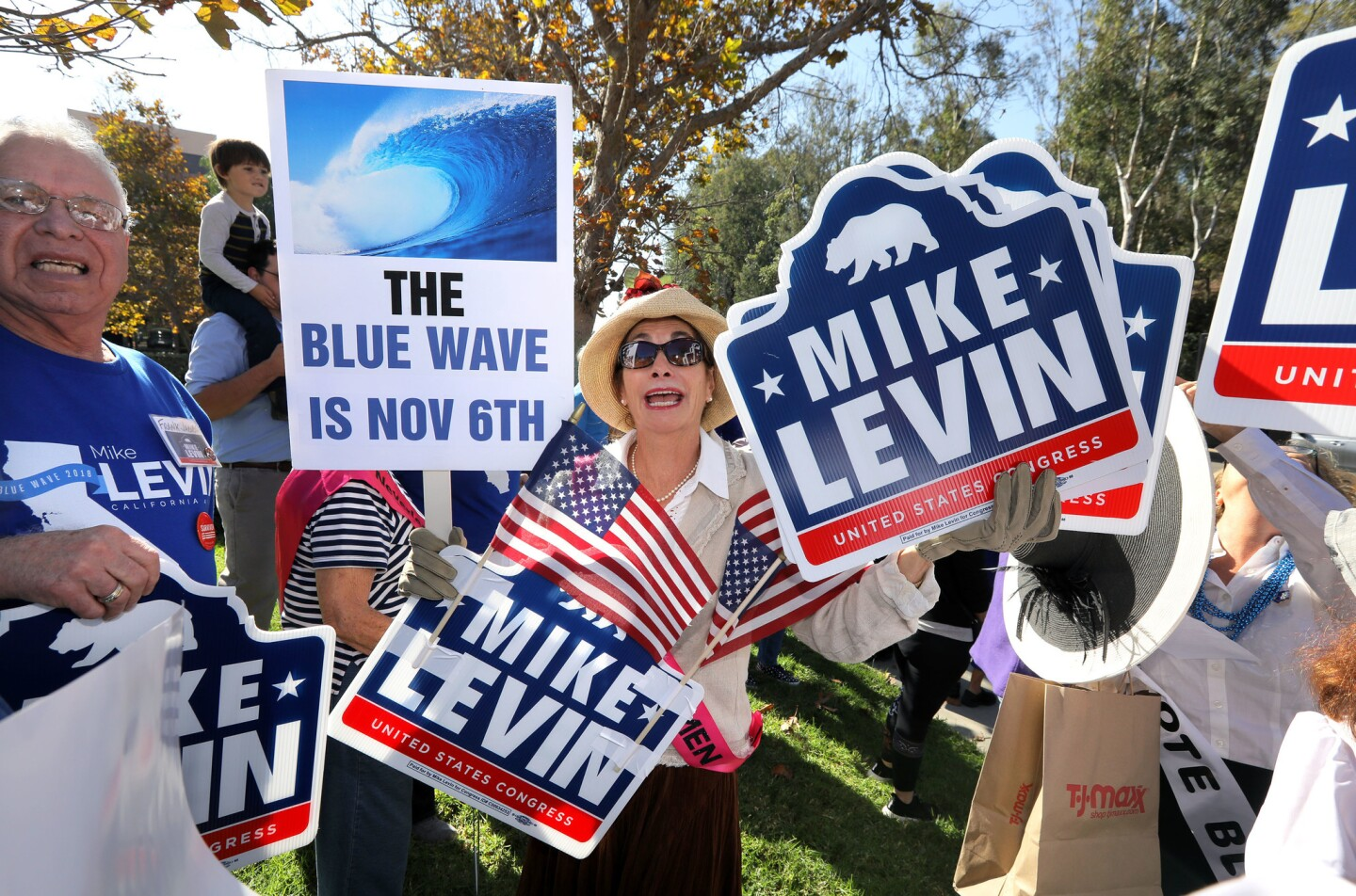 Nancy Hardwick, of Encinitas, holds signs supporting Democrat congressional candidate Mike Levin as she waits for him arrive to a campaign rally outside the offices of outgoing Republican Congressman Darrell Issa.