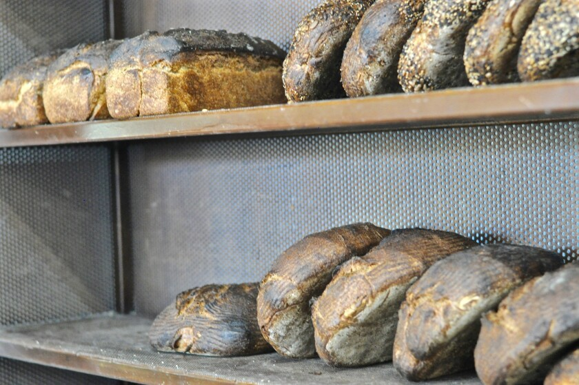 Loaves of spelt, whole wheat and seeded bread sit on the shelves beside the deck oven at Lodge Bread in Culver City.