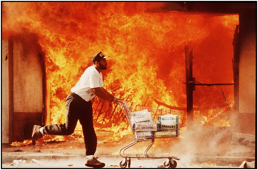 On the second day of rioting, a man runs past a burning Jon's market with a shopping cart full of diapers.