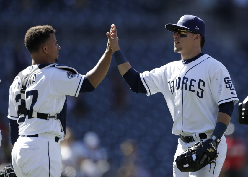 Padres second baseman Luis Urias, right, celebrates with catcher Francisco Mejia after the Padres defeated the Tampa Bay Rays 7-2 in a baseball game Wednesday, Aug. 14, 2019, in San Diego.