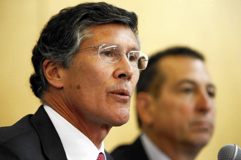CIT Group Chief Executive John Thain, left, and OneWest CEO Joseph Otting speak Thursday at a hearing in Los Angeles about the $3.4-billion takeover of OneWest Bank in Pasadena by New York commercial lender CIT Group.
