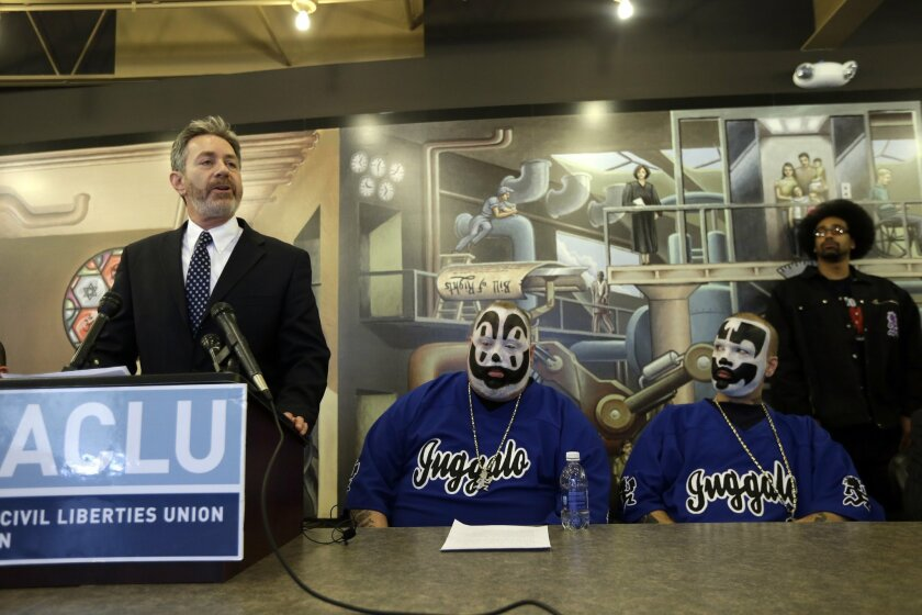 Michael J. Steinberg, legal director for the ACLU of Michigan addresses the media as Joseph Bruce aka Violent J, center, and Joseph Utsler aka Shaggy 2 Dope, members of the Insane Clown Posse listen in Detroit, Wednesday, Jan. 8, 2014. The rap metal group sued the U.S. Justice Department on Wednesd