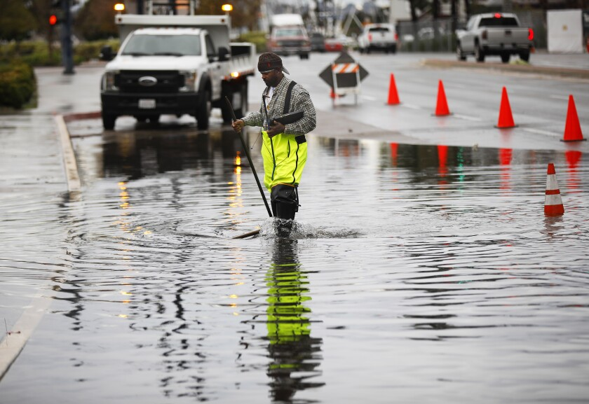 Douglas Owens, with the City of San Diego, monitors an area that flooded along Harbor Boulevard in downtown San Diego on Dec. 23, 2019. The area backs up with water when it rains and there is a high tide.