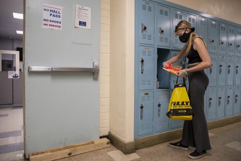 A student wearing a mask at her locker in school