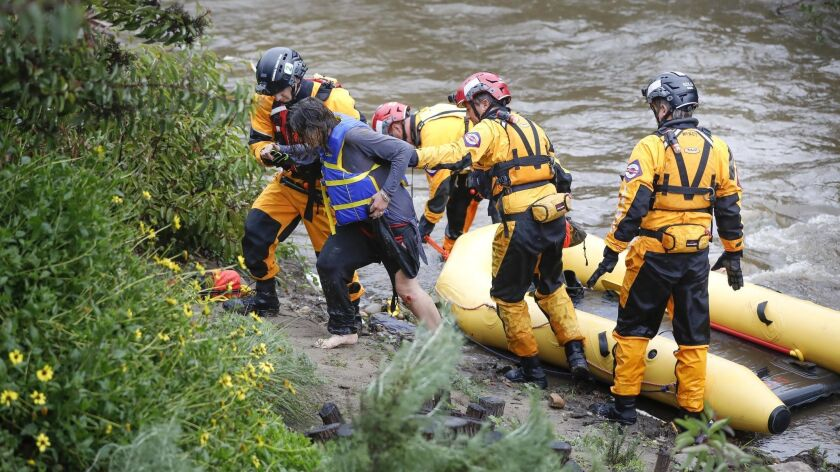 Members of the San Diego Fire Rescue Lifeguards assist a woman out of a raft after she went into Chollas Creek behind Charles Lewis III Memorial Park on Home Avenue.