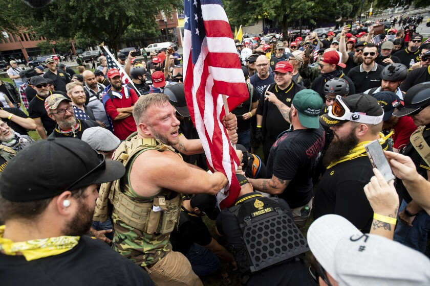 Members of the Proud Boys and other right-wing groups plant a U.S. flag in Portland's Tom McCall Waterfront Park