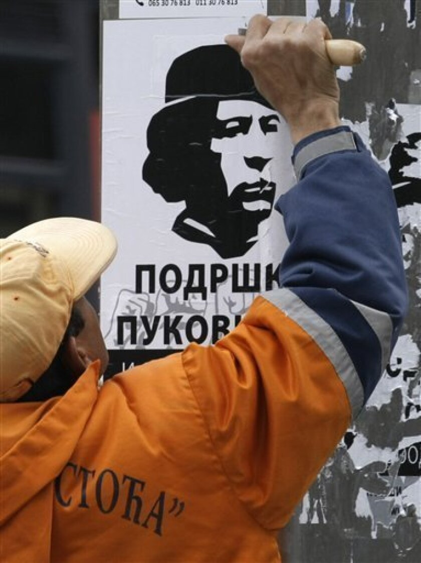"A sweeper cleans a poster showing Libyan leader Moammar Gadhafi and reading ""Support for Gadhafi"", in Belgrade, Serbia, Tuesday, April 5, 2011. Serb support for the Libyan leader grows amid an escalating war in the country that reminds them of their own suffering under NATO bombs.(AP Photo/Darko Vojinovic)"