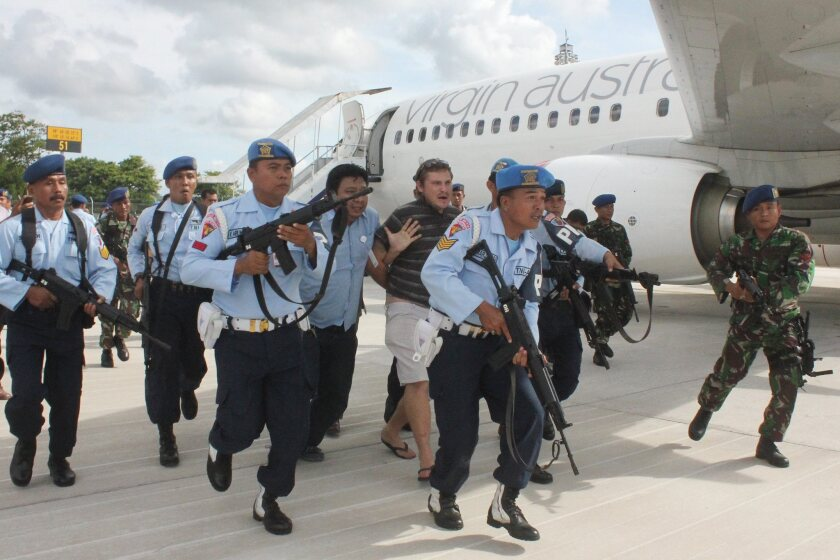 Indonesian troops at Bali's Denpasar airport escort a detained Australian passenger away from a Virgin Australia 737-800 that was the subject of a hijack alert on a flight from Brisbane.