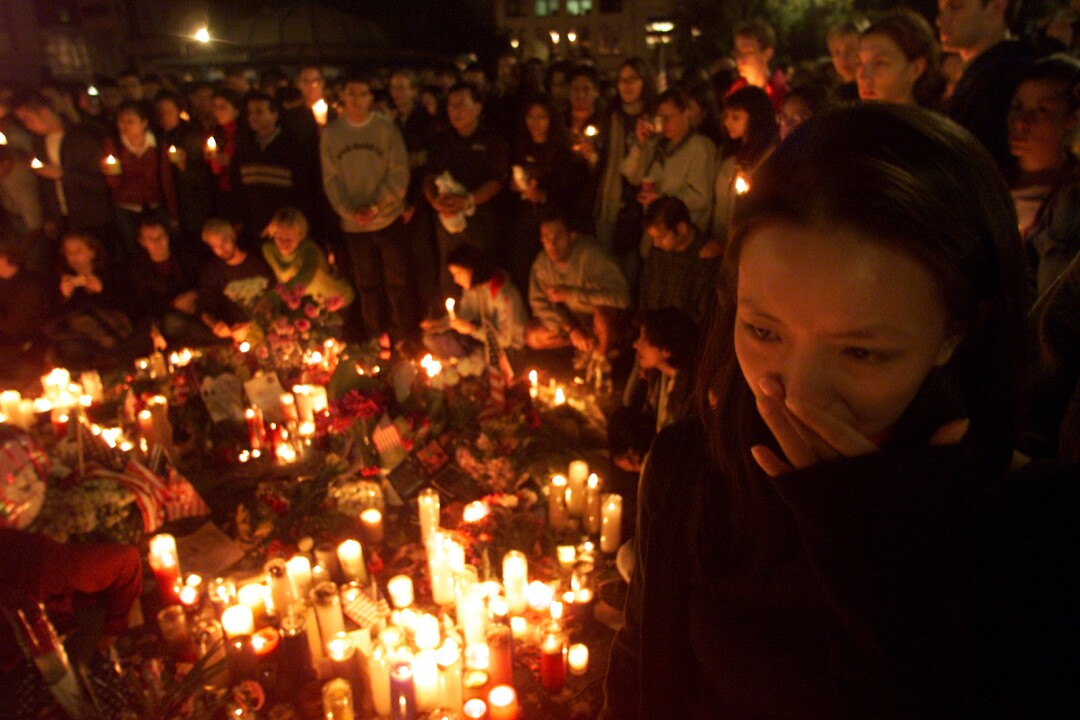 A woman, left foreground, stands among a group encircling candles and flowers