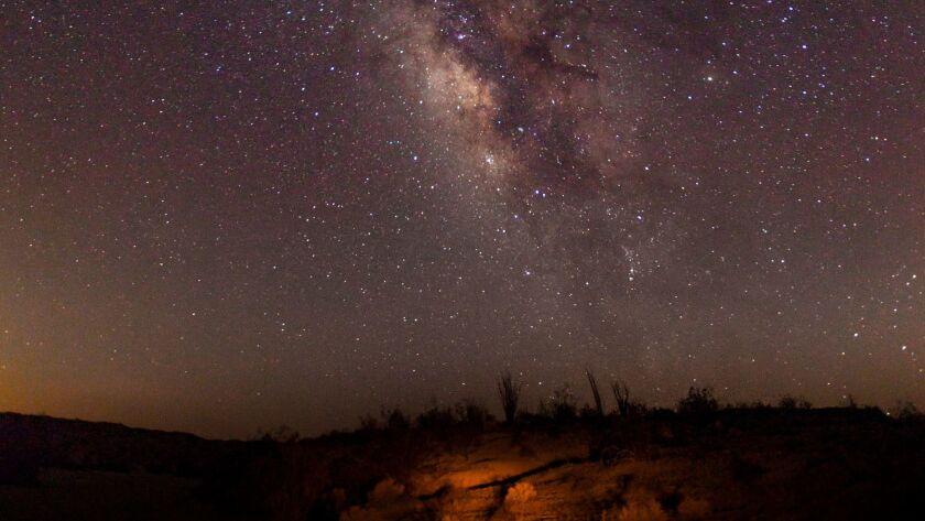 The summer Milky Way and the streak of a passing iridium communications satellite.