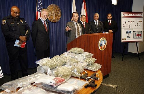 San Diego County Deputy Dist. Atty. Damon Mosler, at lectern, chief of the district attorney's narcotics division, points to the guns and drugs seized during the arrest of 96 people, including 75 students at San Diego State, on drug charges after an extensive undercover investigation called Operation Sudden Fall.