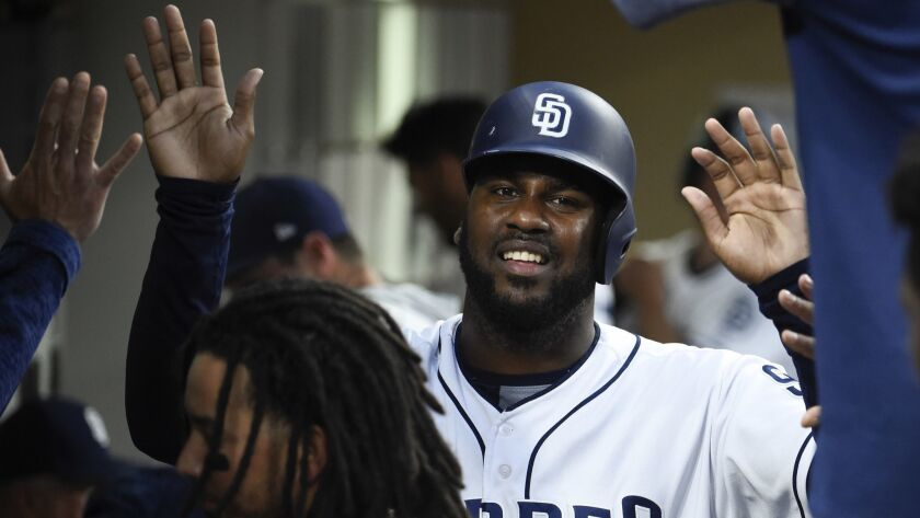 Padres' Franmil Reyes is congratulated after scoring during the second inning of a baseball game against the Oakland Athletics at Petco Park on June 19.