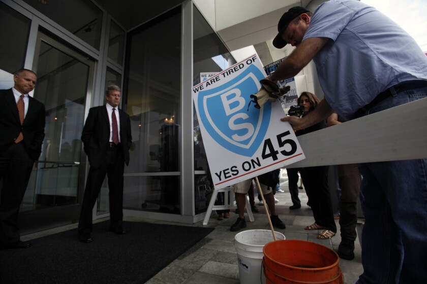 Security guards watch as Jamie Court of the Consumer Watchdog organization places a sign into buckets filled with steer manure outside Blue Shield offices in El Segundo on Oct. 14. The odoriferous message was delivered by Proposition 45 supporters protesting Blue Shield sponsorship of anti-Proposition 45 commercials.