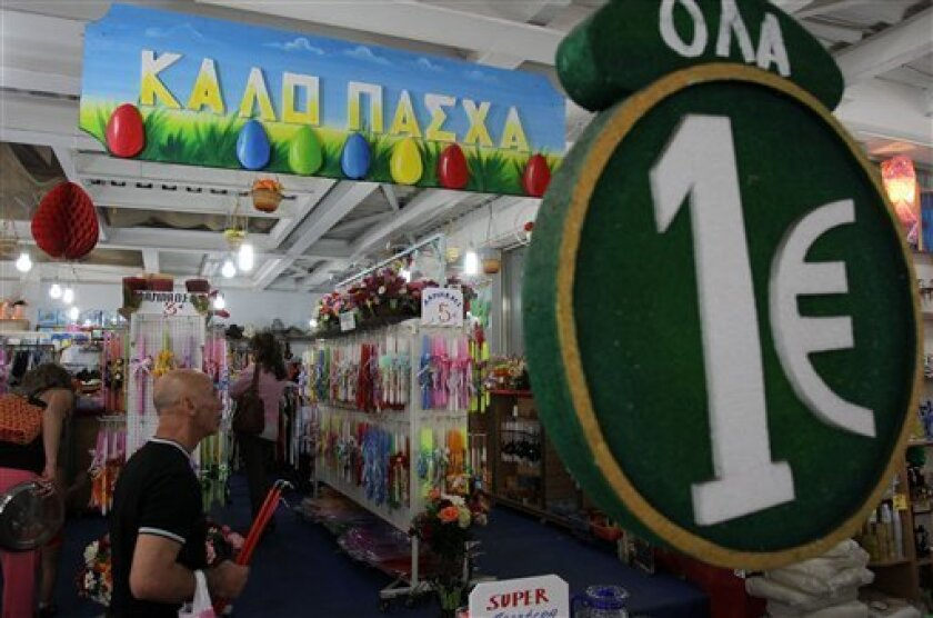 """A one-euro sign and a banner reading """"Happy Easter"""" are displayed at a discount store selling candles and other items at the start of Orthodox Holy Week, in Athens, Monday, April 29, 2013. Orthodox Christians around the world celebrate Easter on Sunday, May 5. Retailers and travel agents booking domestic trips are expecting slower sales over the Easter holidays, with a continued recession expected to see Greece's crisis-hit economy contract a further 4.25 percent this year. (AP Photo/Thanassis S"""