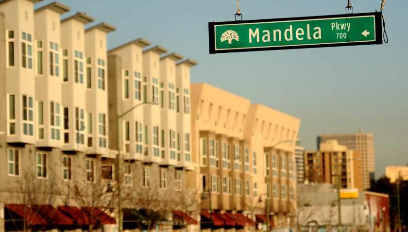 A street sign for Mandela Parkway is in sharp focus, with the Mandela Gateway apartments in Oakland in the background.