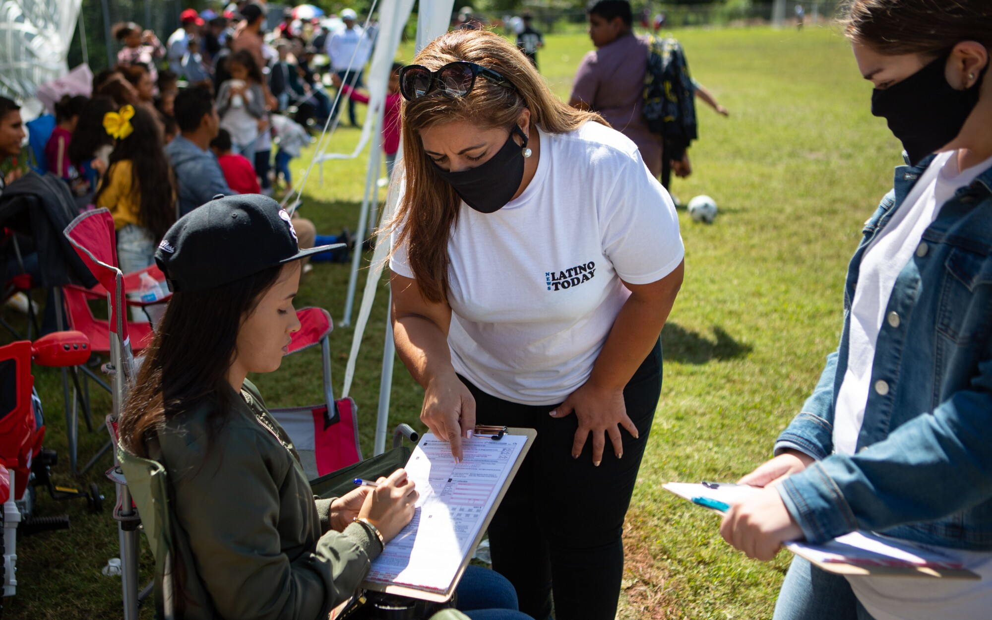 Sandra Amado Gómez and her daughter Aylen Agostina Gómez register a woman to vote at a soccer game in Raleigh, N.C.