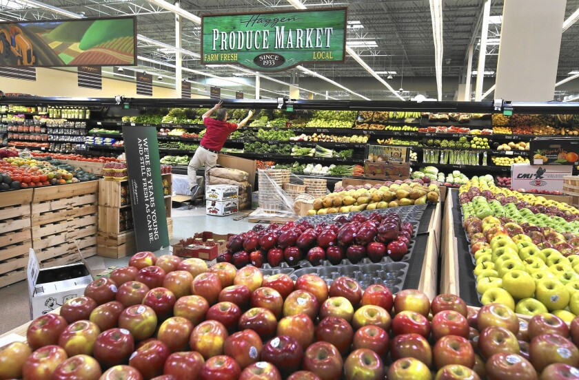 A worker checks the misters in the produce department of a Haggen grocery store that was formerly an Albertsons in Palmdale.