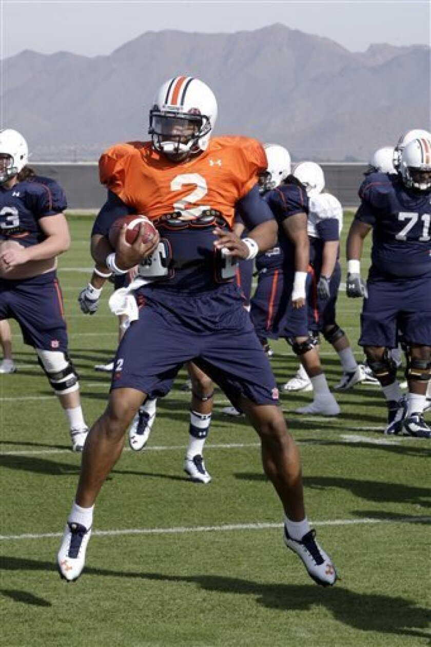 Auburn's Cam Newton warms up with teammates during NCAA college football practice Thursday, Jan. 6, 2011, in Scottsdale, Ariz. Auburn is scheduled to play Oregon in the BCS championship on Monday, Jan. 10, in Glendale, Ariz. (AP Photo/Ross D. Franklin)