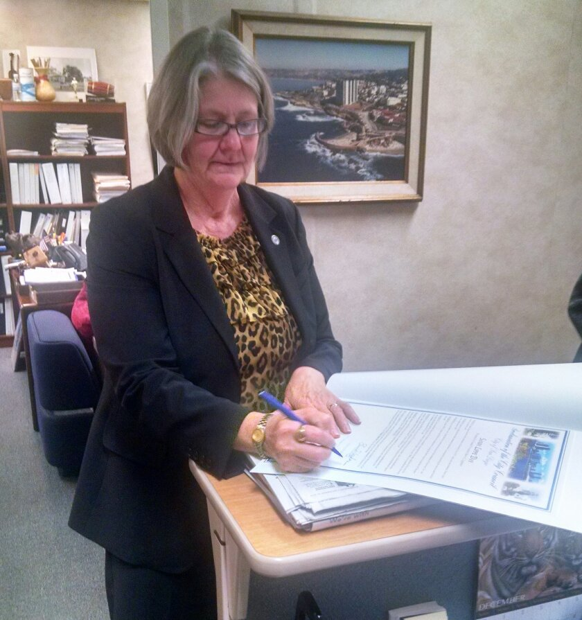 District 1 City Councilmember and La Jolla Shores resident Sherri Lightner signs her first document as the newly elected president of the San Diego City Council.
