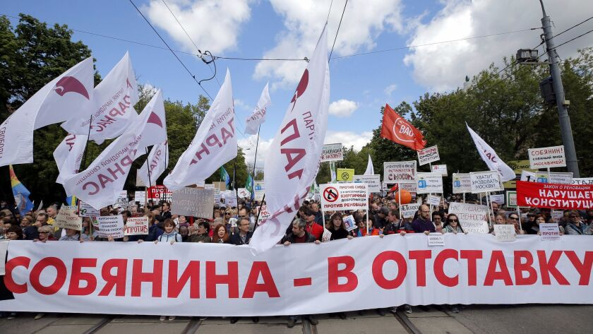 epa05995487 Muscovites hold a poster read 'Sobyanin should resign', during a protest rally against t